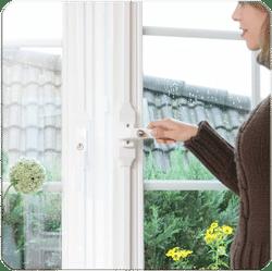 Auf dem Bild ist eine Frau mittleren Alters zu sehen, die ein Fenster öffnet. Dieses Fenster ist mit einem Fensterstangenverschluss abgesichert.