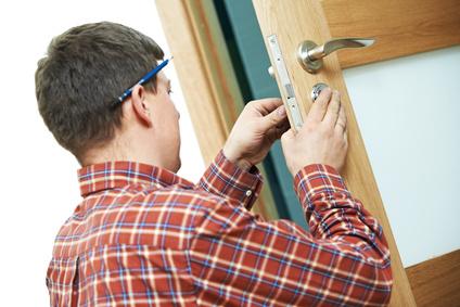 Schlüsseldienst Handwerker wechselt Türschloss aus