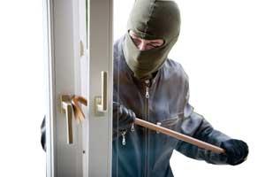 Einbrecher dringt in ein Haus ein in dem er das Fenster aufhebelt.
